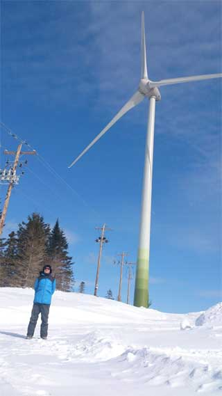 Neal Livingston at the foot of a Black River Wind Turbine